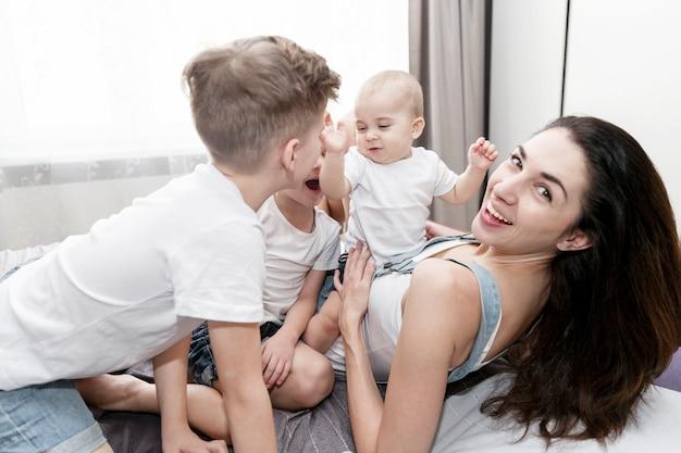 La giovane madre con i suoi figli piccoli è sdraiata sul letto e ride. tenerezza nei rapporti familiari.