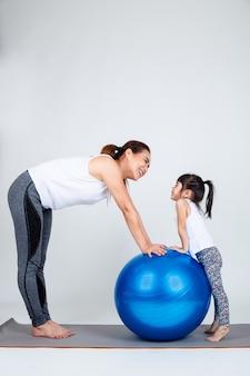La giovane madre con la piccola figlia si esercita sulla palla di forma fisica