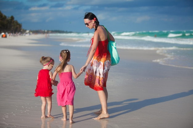 La giovane madre e due i suoi bambini di modo alla spiaggia esotica il giorno soleggiato