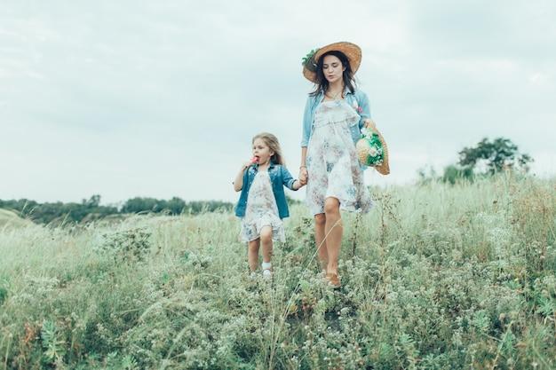 La giovane madre e figlia sull'erba verde