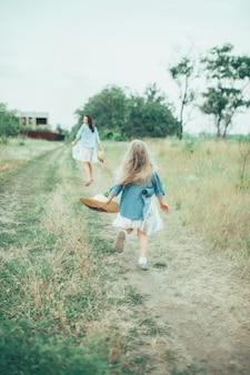 La giovane madre e figlia sullo spazio di erba verde