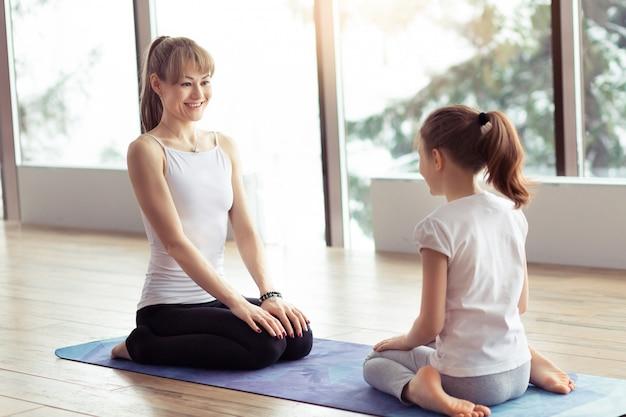 La giovane madre e il bambino che fanno l'yoga o che allungano la forma fisica si esercitano insieme