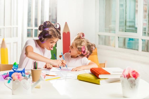 La giovane madre e la figlia piccola disegnano con le matite a casa