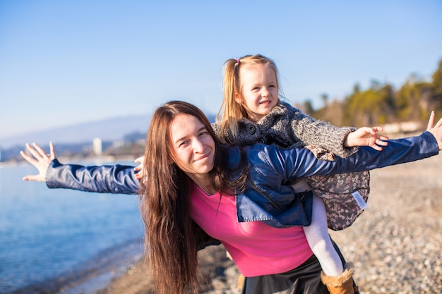 La giovane madre e la piccola figlia adorabile che volano come un uccello all'inverno tirano