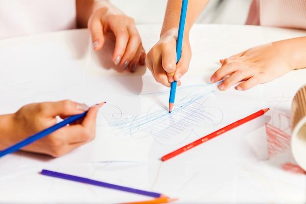 La giovane madre e la sua figlioletta disegnano con le matite a casa