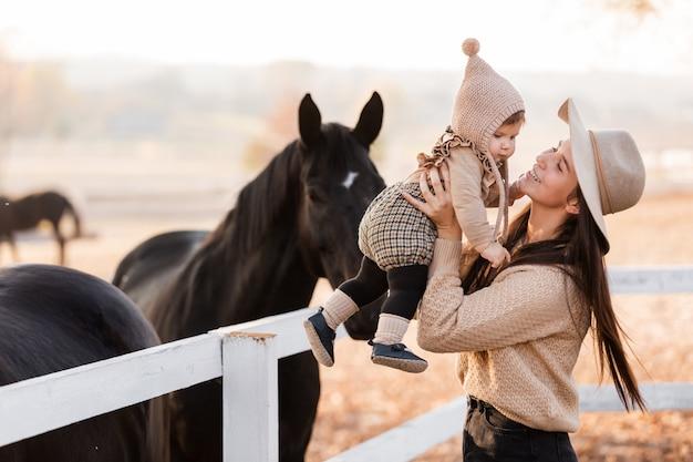 La giovane madre felice sta giocando con la piccola figlia del bambino vicino ai cavalli nel parco di autunno