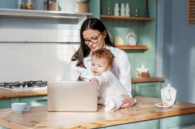 La giovane madre lavora a casa con un computer portatile con un bambino in braccio