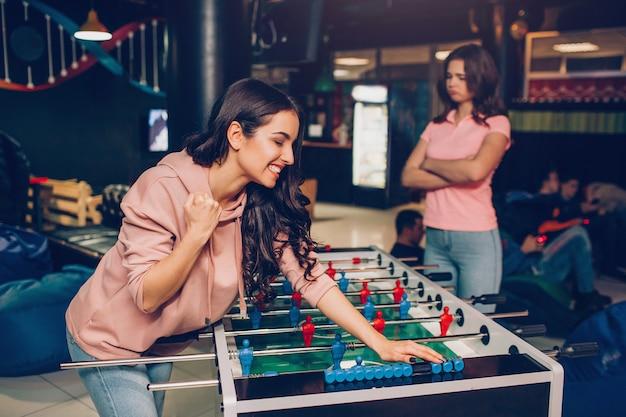 La giovane magra felice magra per presentare il calcio nella stanza di gioco. la sua amica è arrabbiata. lei tiene le mani incrociate.