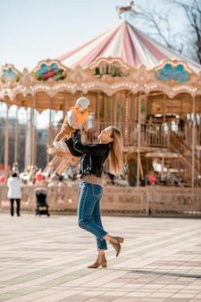 La giovane mamma alla moda cammina con il bambino nel parco. mamma felice