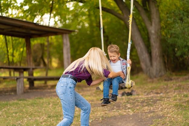 La giovane mamma bionda scuote il suo piccolo figlio su un'altalena in un parco verde. infanzia felice.