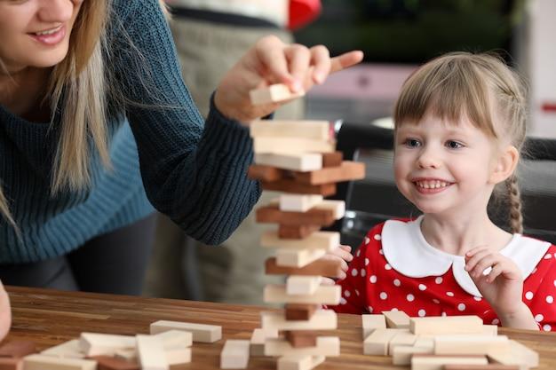 La giovane mamma con la piccola figlia gioca in blocco di legno