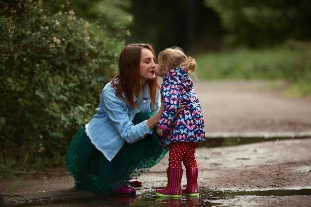 La giovane mamma e la piccola figlia si divertono camminando negli stivali di gomma sulle piscine in parco