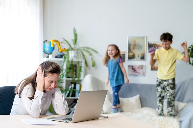 La giovane mamma lavora a casa con il portatile, insieme a due bambini. vogliono saltare