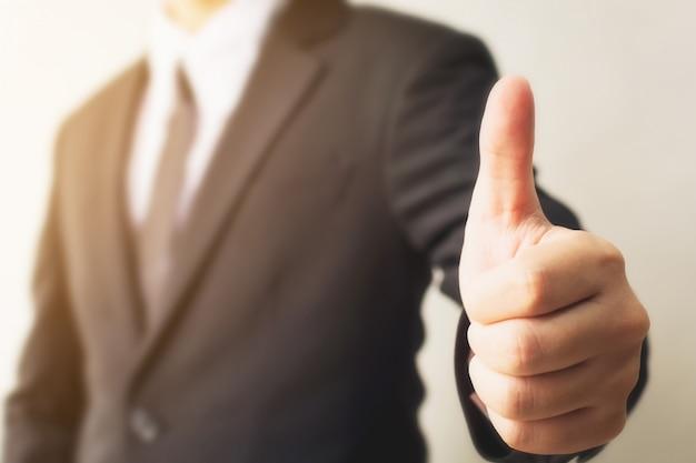 La giovane mano dell'uomo d'affari che mostra il pollice sul segno gesture