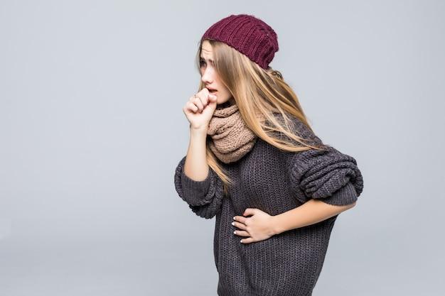 La giovane modella vestita di moda ha mal di testa e di stomaco su grigio