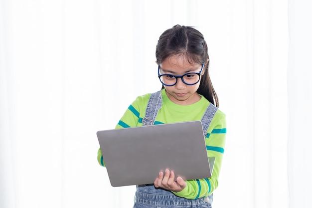 La giovane piccola scolara asiatica con i vetri dell'occhio concentra i compiti sul computer portatile