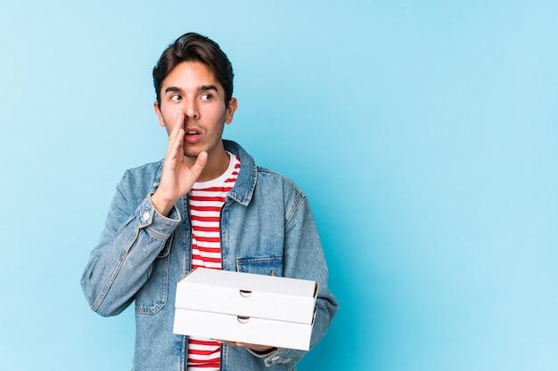 La giovane pizza caucasica della tenuta dell'uomo isolata sta dicendo le notizie di una frenata calde segrete e sta guardando da parte