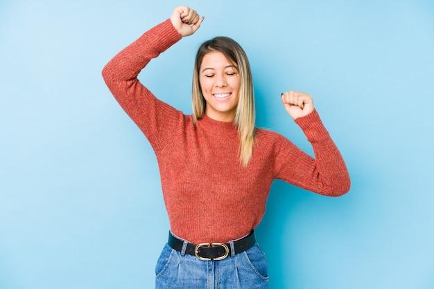 La giovane posa caucasica della donna ha isolato celebrando un giorno speciale, salta e alza le braccia con energia.