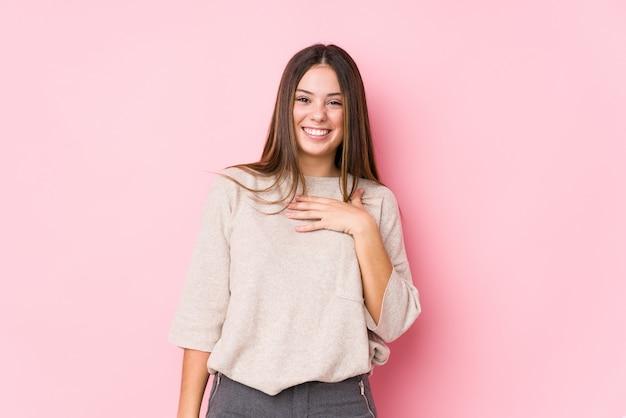 La giovane posa caucasica della donna ride ad alta voce tenendo la mano sul petto.