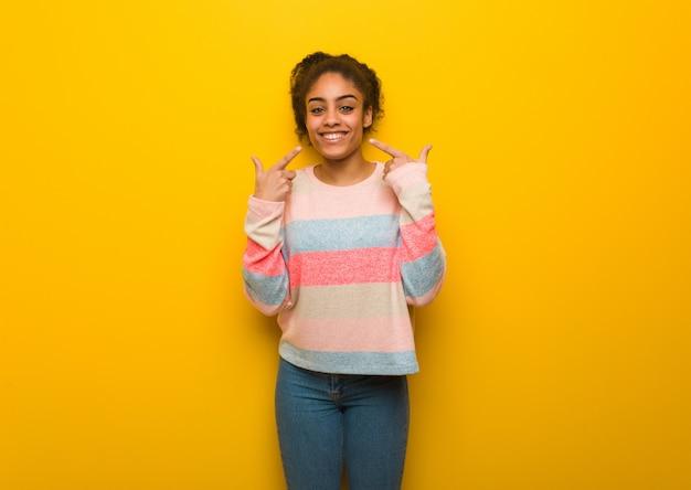 La giovane ragazza afroamericana nera con gli occhi azzurri sorride, indicando la bocca