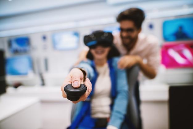 La giovane ragazza allegra sta usando i sistemi vr e punta i controller verso la telecamera mentre un giovane la tiene in braccio.