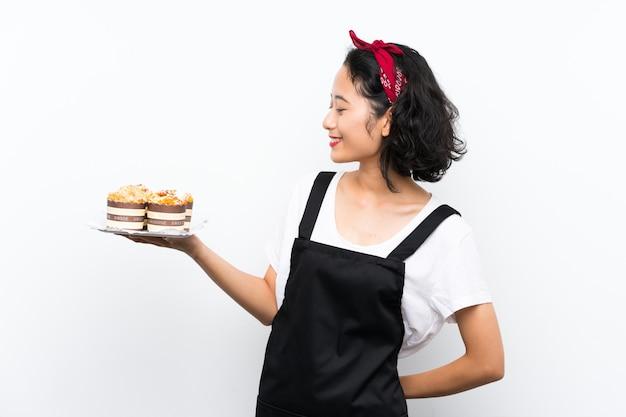 La giovane ragazza asiatica che tiene i lotti del muffin agglutina sopra la parete bianca isolata con l'espressione felice