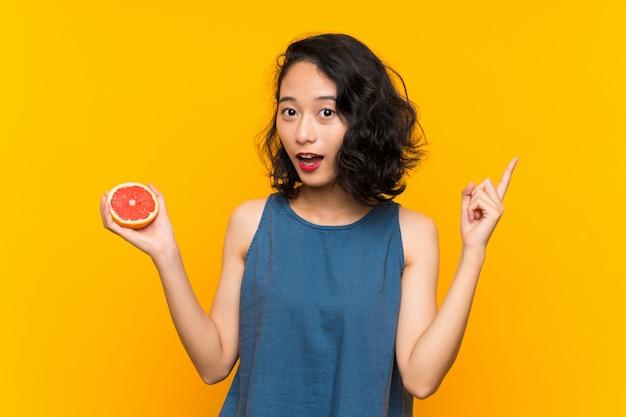 La giovane ragazza asiatica che tiene un pompelmo che intende realizzare la soluzione