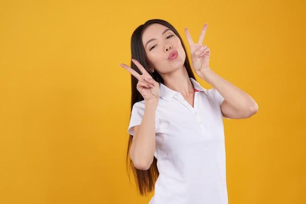 La giovane ragazza asiatica sta posando allegro isolata