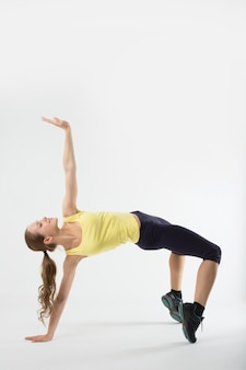 La giovane ragazza atletica fa il ponte relativo alla ginnastica, isolato sulla parete bianca