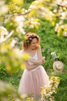 La giovane ragazza attraente cammina nel parco verde di primavera che gode della natura di fioritura. ragazza sorridente in buona salute che fila sul prato inglese della molla. allergia senza