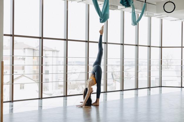 La giovane ragazza attraente che fa la forma fisica si esercita con yoga sul pavimento contro la superficie delle finestre panoramiche