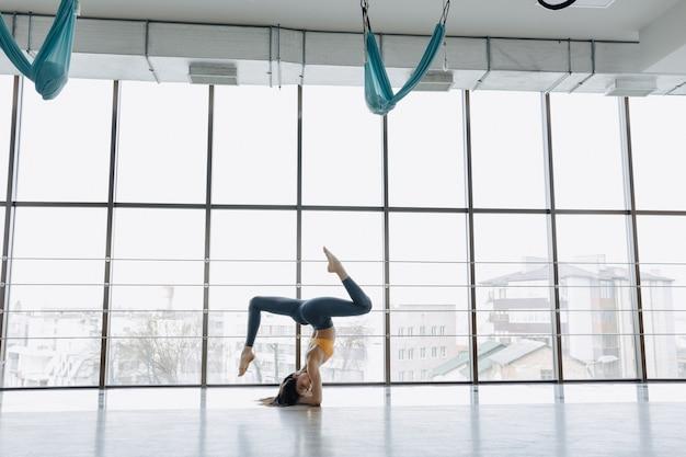 La giovane ragazza attraente che fa la forma fisica si esercita con yoga sul pavimento. finestre panoramiche