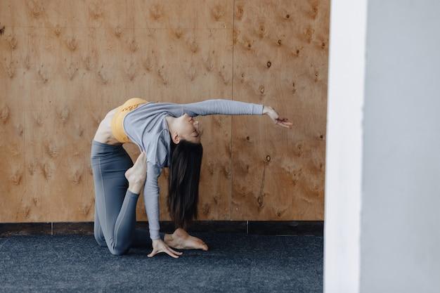 La giovane ragazza attraente che fa la forma fisica si esercita con yoga sul pavimento