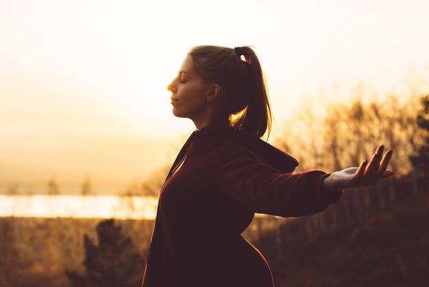 La giovane ragazza attraente in natura durante il tramonto gode dell'aria fresca