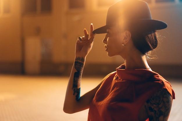 La giovane ragazza attraente in un cappello pone alla telecamera di notte