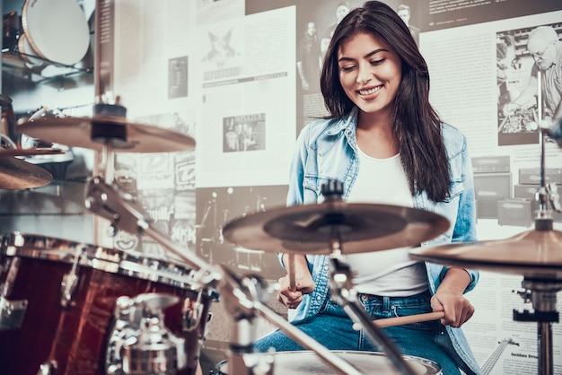 La giovane ragazza attraente sta giocando sul kit di batteria nel negozio di musica