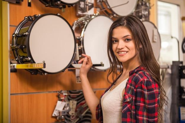 La giovane ragazza attraente sta scegliendo i tamburi nel negozio di musica.