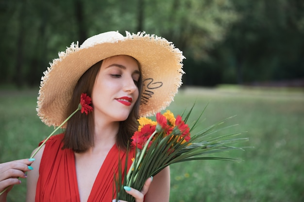 La giovane ragazza attraente tiene un mazzo di fiori di campo estivi.