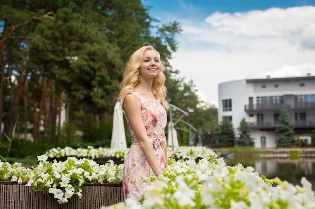 La giovane ragazza bionda affascinante gode della bellezza della natura nel parco