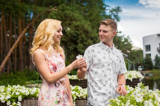 La giovane ragazza bionda affascinante sta flirtando e con un ragazzo nel giardino. storia d'amore di una coppia innamorata