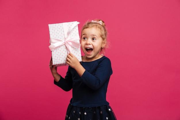 La giovane ragazza bionda allegra che tiene il contenitore di regalo e si rallegra