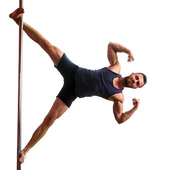 La giovane ragazza bionda atletica che fa la forza si esercita su un pilone. pole dance