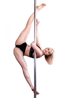 La giovane ragazza bionda atletica che fa la forza si esercita su un pilone.