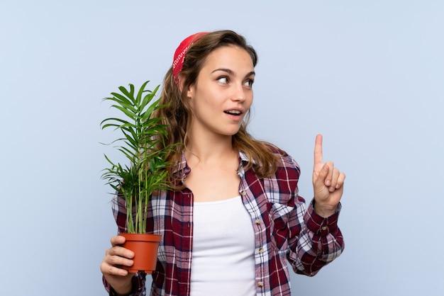La giovane ragazza bionda del giardiniere che tiene una pianta che intende realizzare la soluzione mentre solleva un dito su