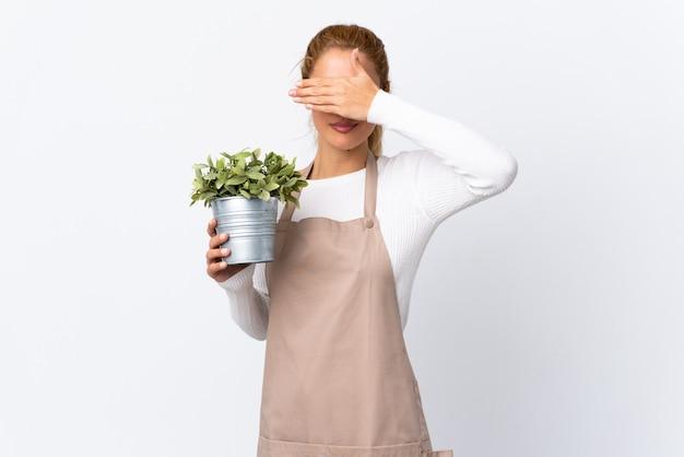 La giovane ragazza bionda della donna del giardiniere che tiene una pianta sopra la copertura bianca isolata osserva a mano