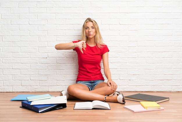 La giovane ragazza bionda dello studente con molti libri sul pavimento che mostra il pollice giù firma