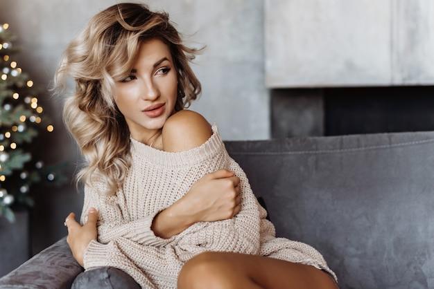 La giovane ragazza bionda sexy del primo piano si siede su un sofà in un maglione