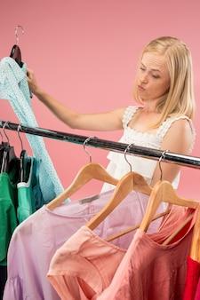 La giovane ragazza carina infelice guarda i vestiti e prova mentre sceglie al negozio