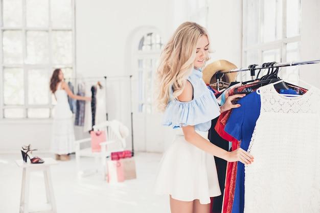 La giovane ragazza carina scegliendo e provando abiti in negozio