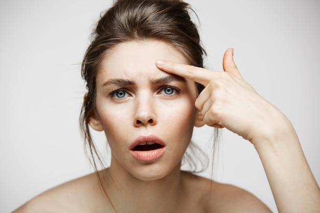 La giovane ragazza castana ha dispiaciuto della sua pelle del fronte dell'acne di problema sopra fondo bianco. cosmetologia della salute e cura della pelle.